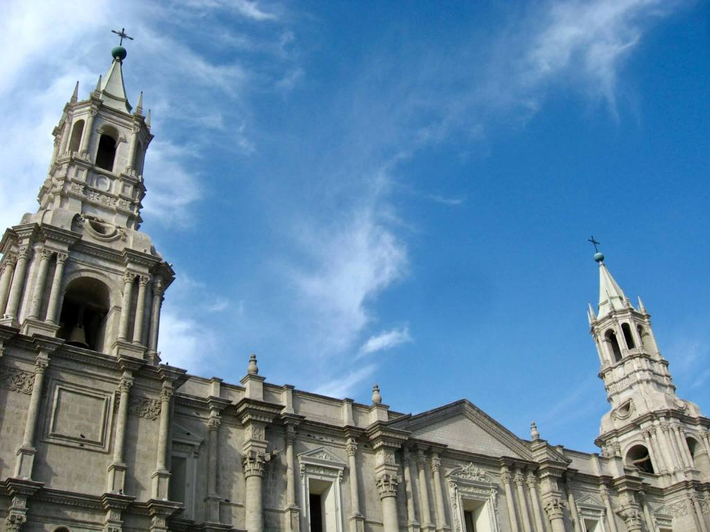 The white cathedral towers of Arequipa against a bright blue sky