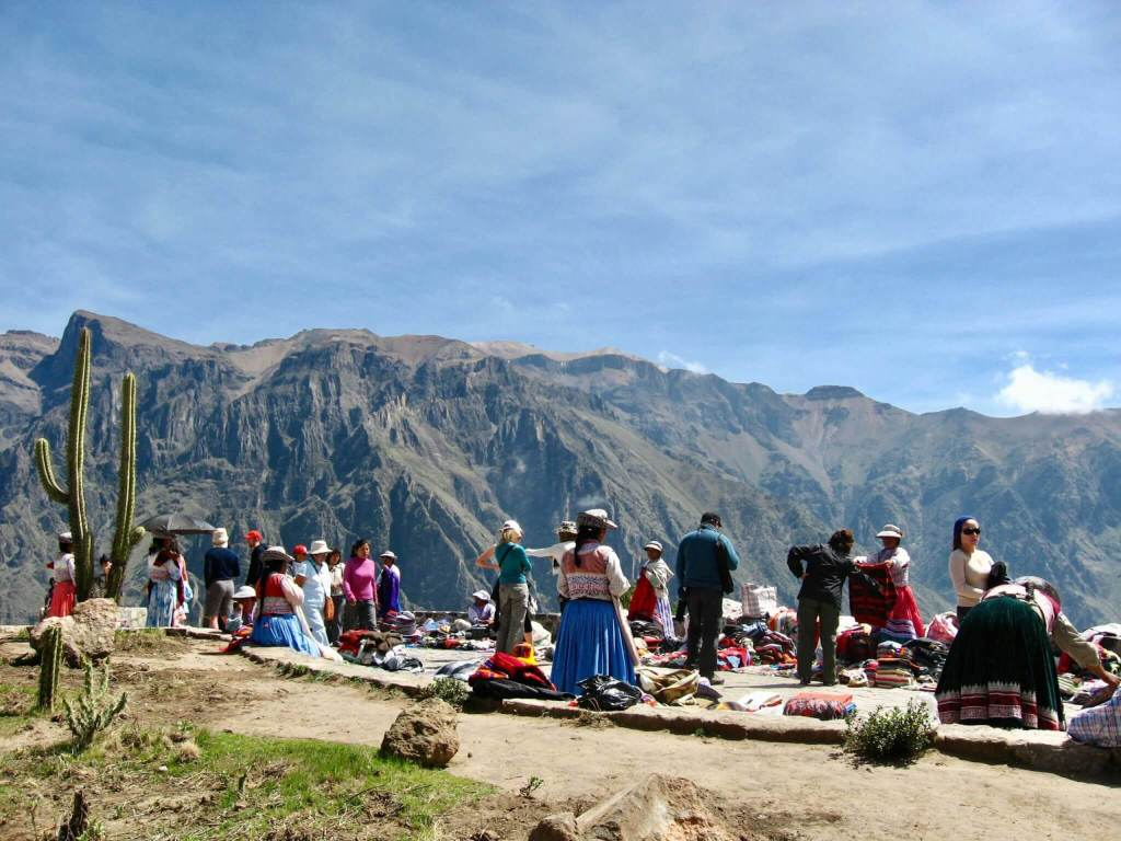 Indigenous women in traditional dress selling handicrafts and snacks along the canyon's rim