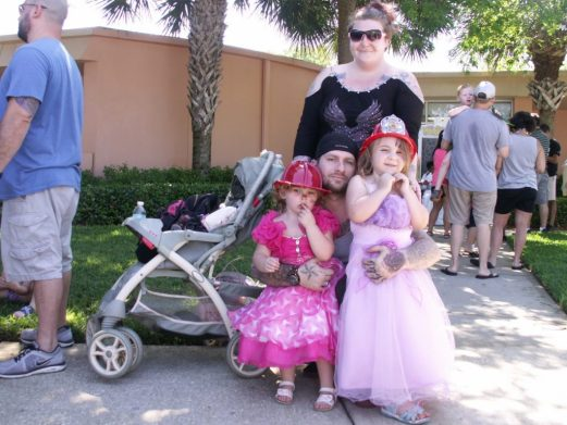 """Sisters Donelle, 3, left, and Skyla, 4, wearing their Easter gowns and fire hats, pose with their parents Michelle Peters and Donovan Molisee after having their picture taken with the Easter Bunny Saturday at Gulfport's Recreation Center. """"It's really nice,"""" Michelle said of the event. """"We really appreciate it."""""""