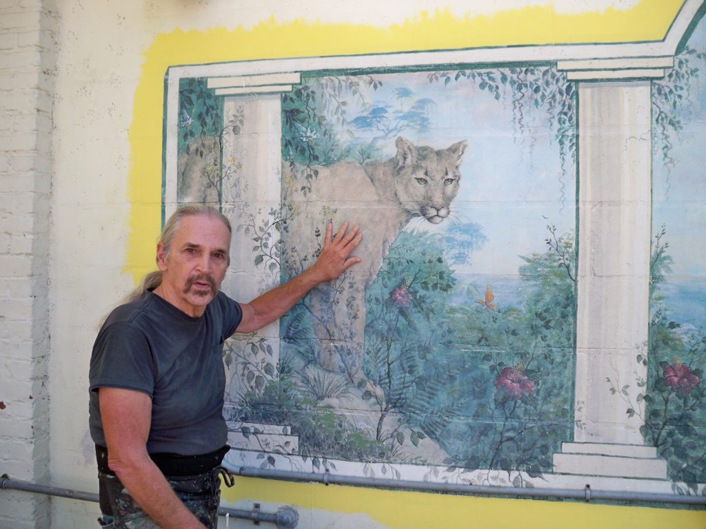 A man in a black t-shirt standing next to a mural of a panther behind white columns