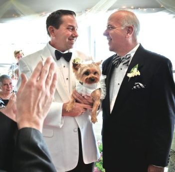 """Thomas Tomlinson and Michael Chapman (with Yorkie """"maid of honor"""" Isabella) met on Valentine's Day, 2012, and in January, became the first same-sex couple to marry at the Gulfport Casino. At the end of the ceremony, the band played """"Time After Time,"""" the couple's wedding theme, from the 1947 film """"An Affair to Remember."""" Photo by Daria Kopylova (DariaKopylova.com)"""