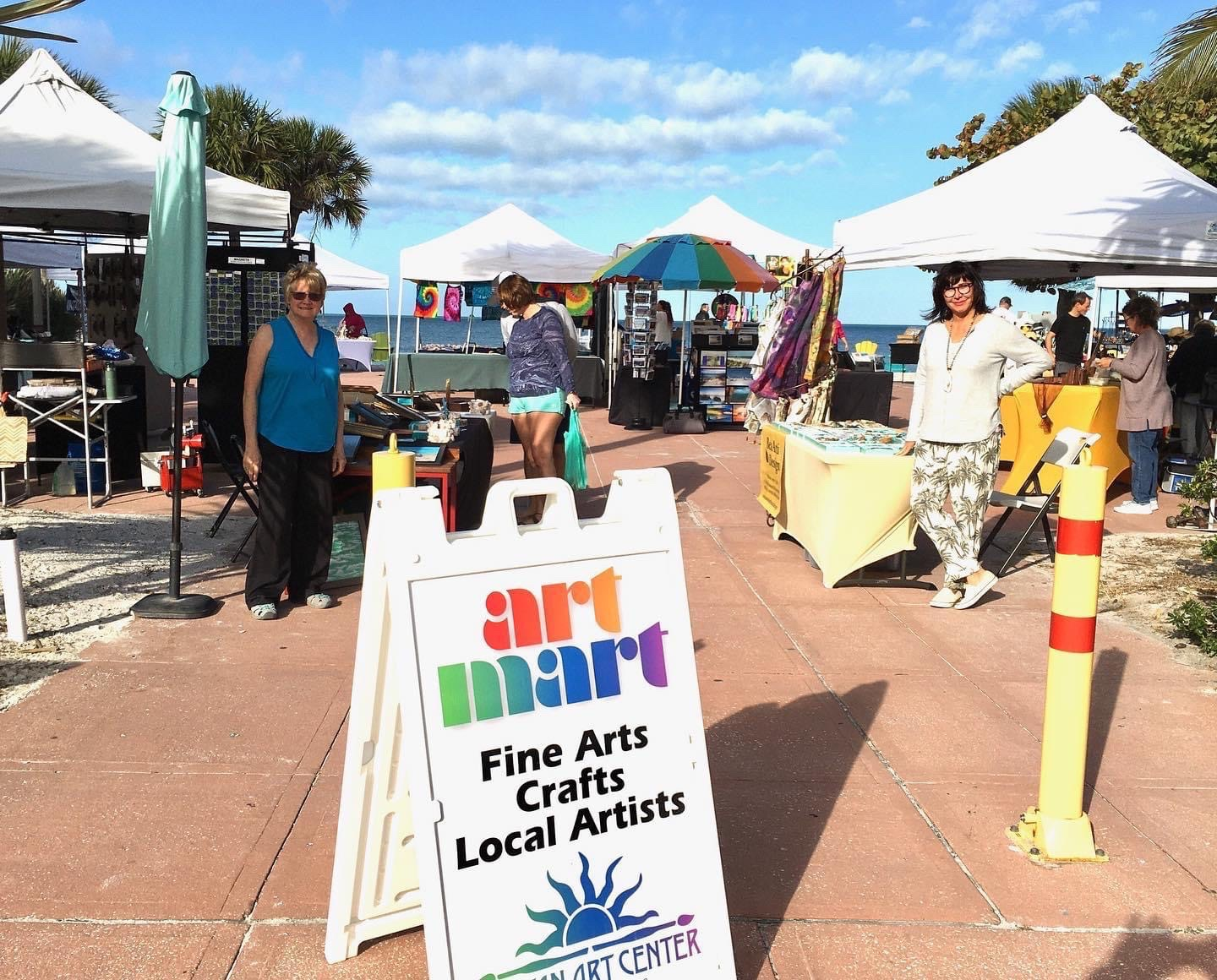 People at the Art Mart Market on a sunny day. with Art Mart sign St. Pete Beach Florida.