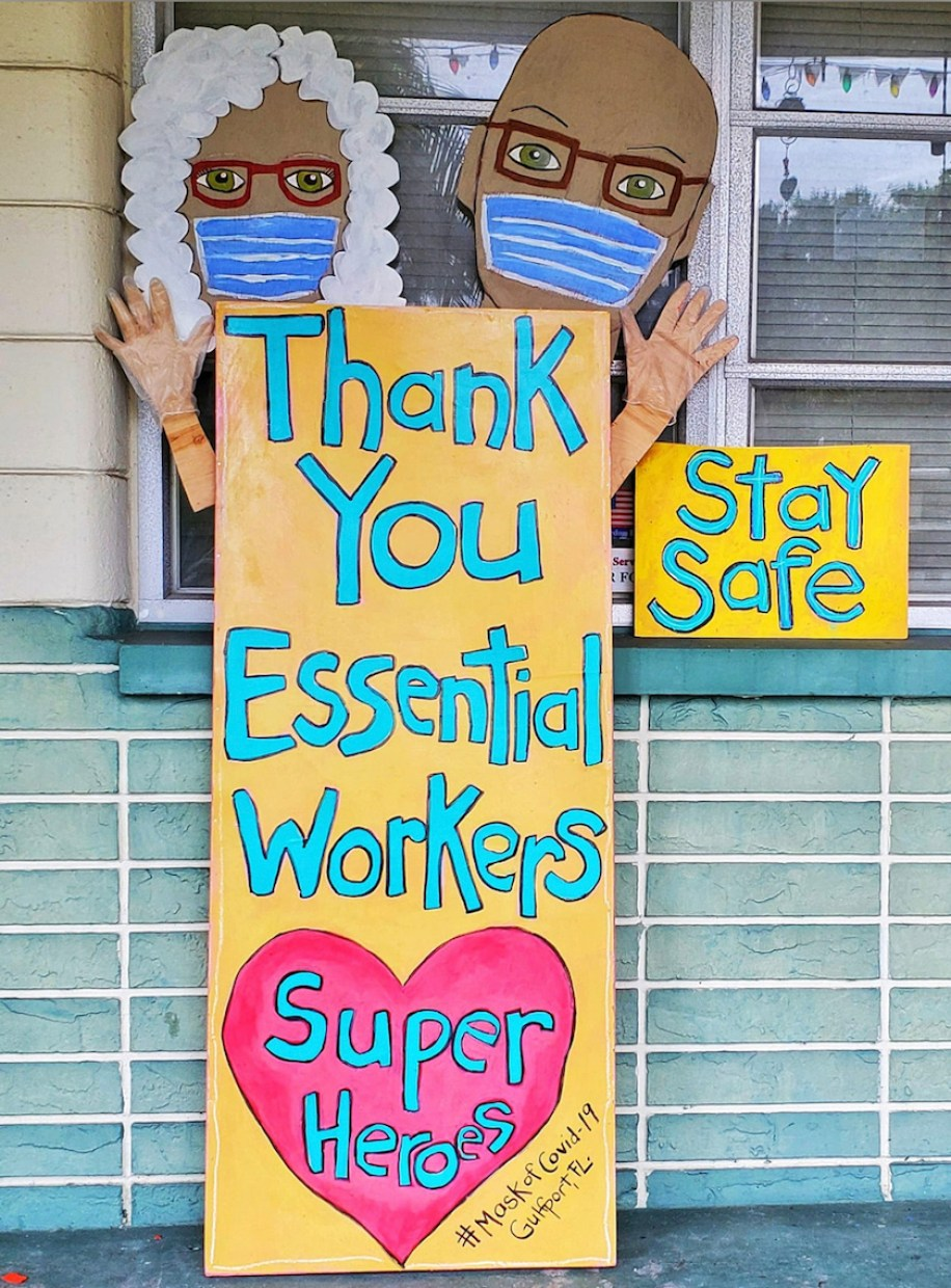 A homemade sign depicting a man and woman with face masks thanking essential workers.