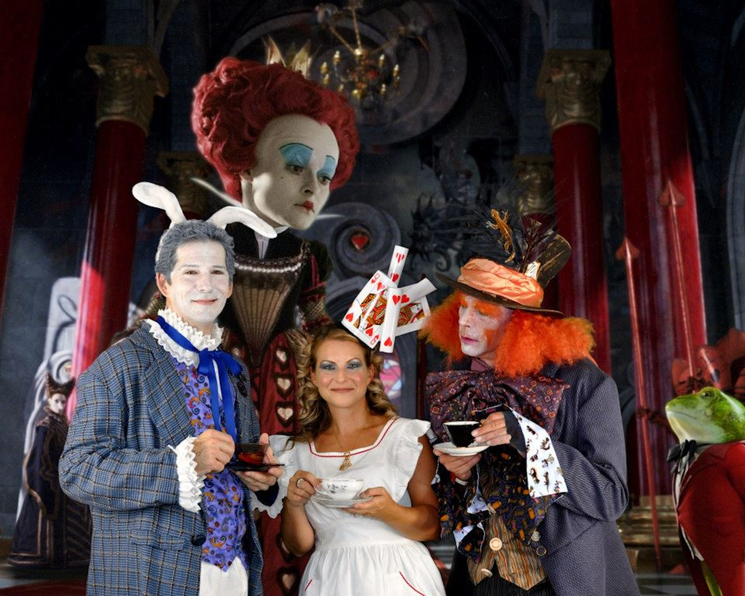 Three people in Alice and Wonderland-themed costumes pose in front of a giant Queen of Hearts background.