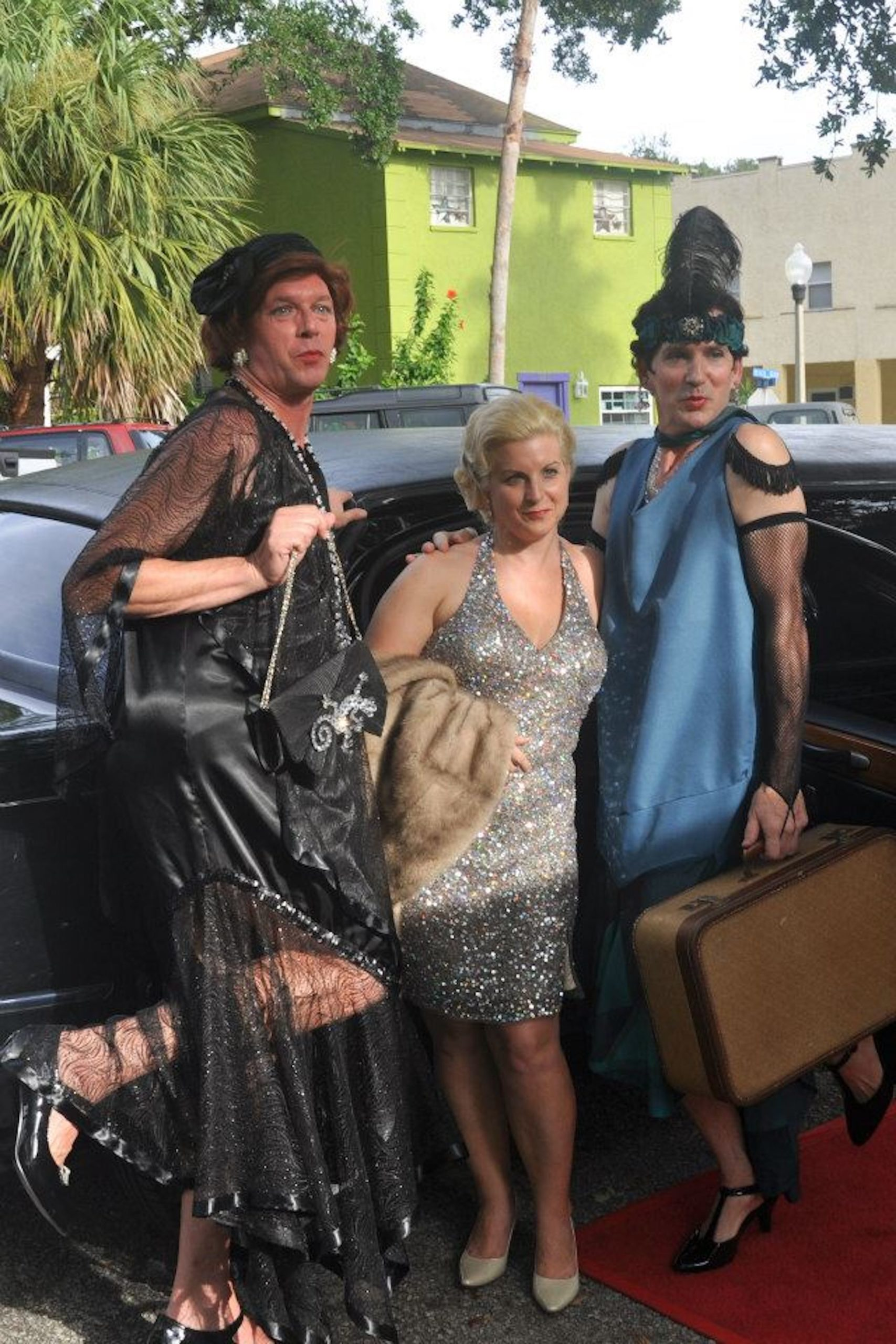 Three people pose in 1920s Flapper costumes in front of a black car.