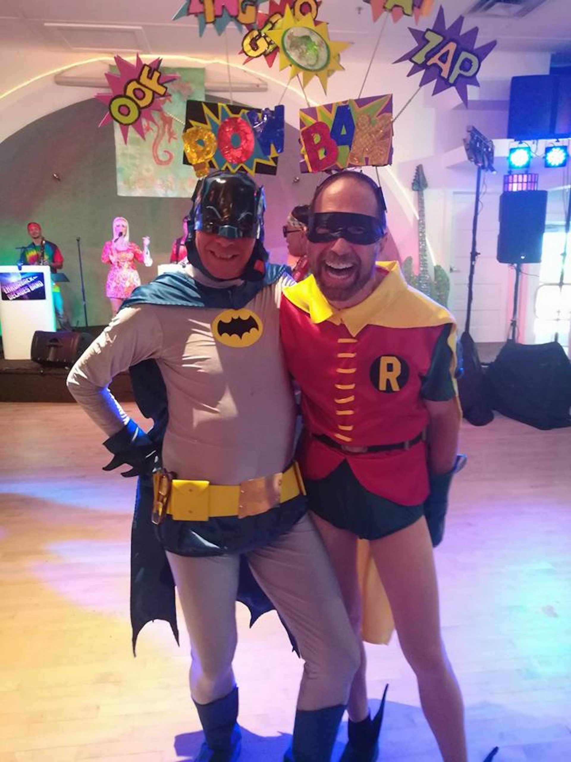 Two men in Batman and Robin costumes smile at the camera