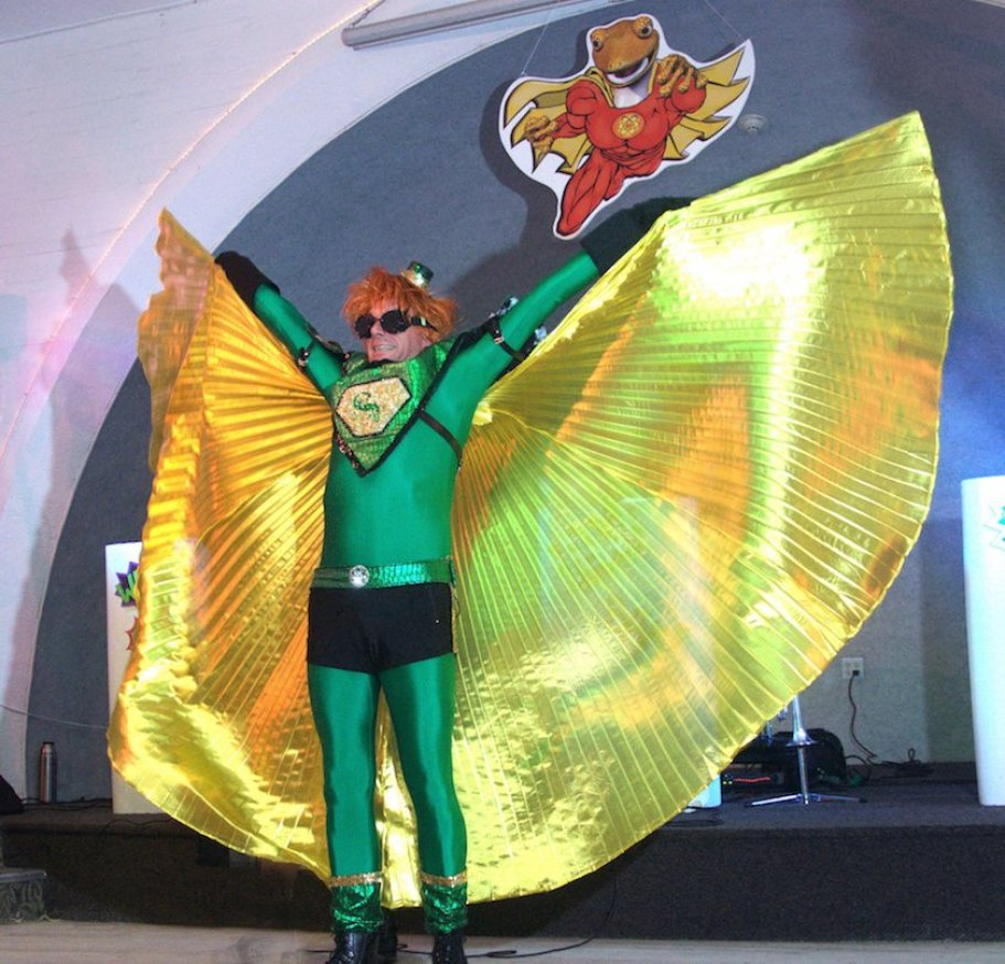 A man in a green superhero costume and gold cap with arms spread wide