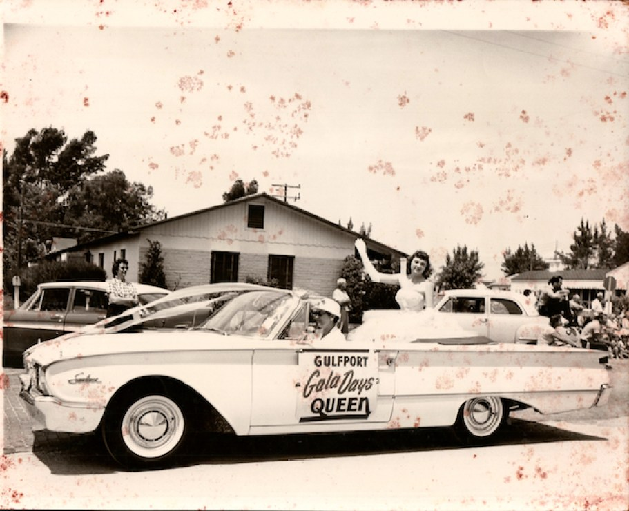 1950s photo of a beauty pageant winner riding in a convertible car.