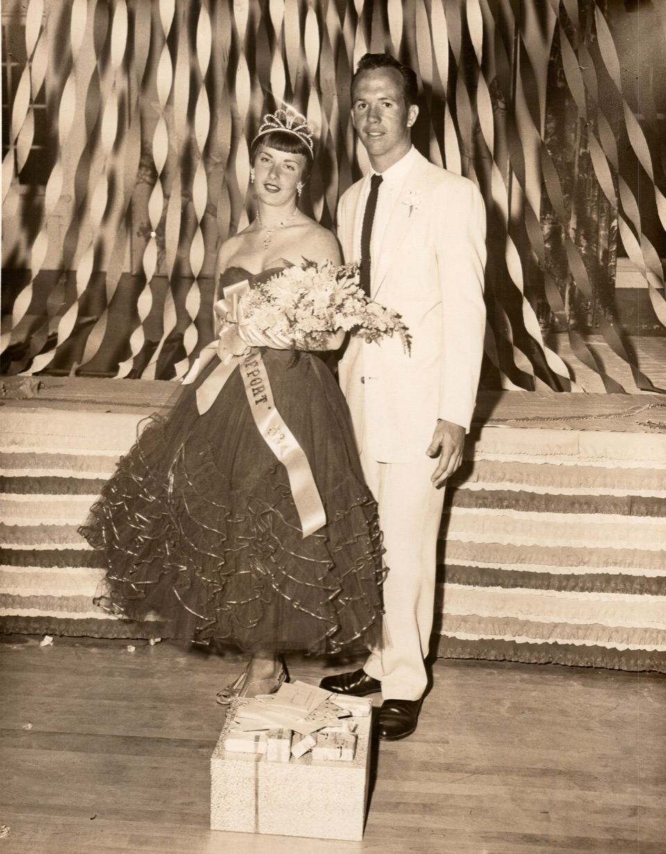 A picture from the 1950s showing a man and woman standing in formal wear with bouquet and sash.
