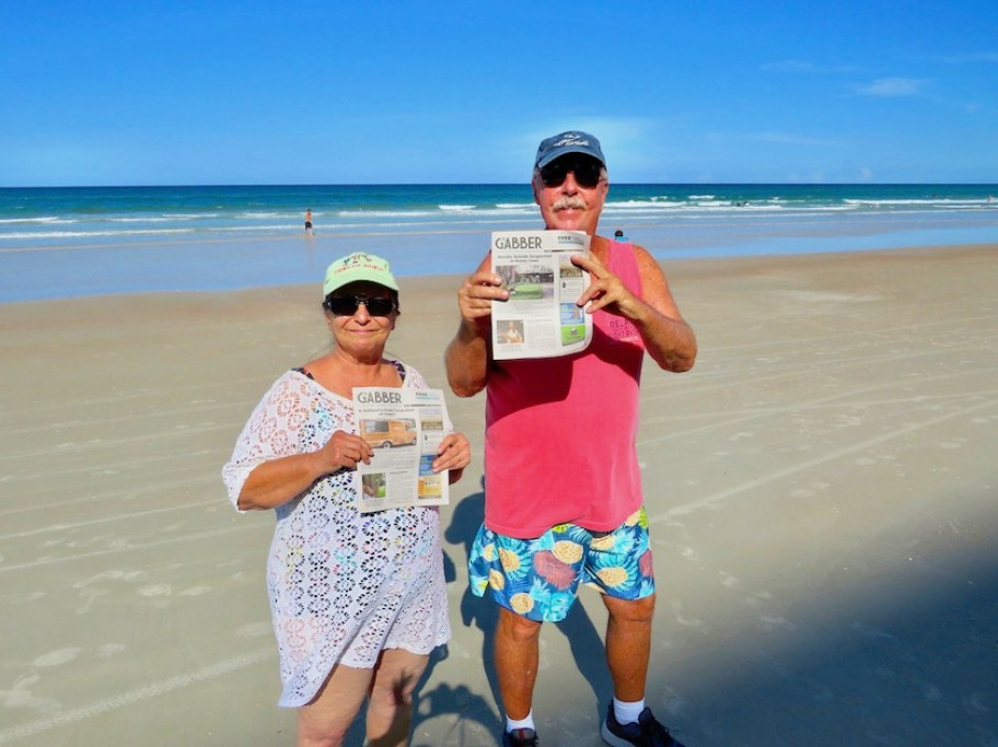 A man in a red shirt and shorts and a woman in a cover-up standing on the beach holding Gabber newspapers.
