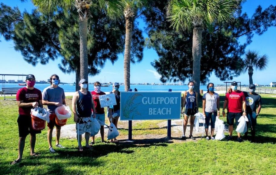 Twenty-nine volunteers by a Gulfport Beach sign on the beach