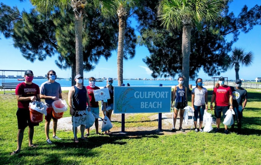 Twenty-nine volunteers by a Gulfport Beach sign on the beach