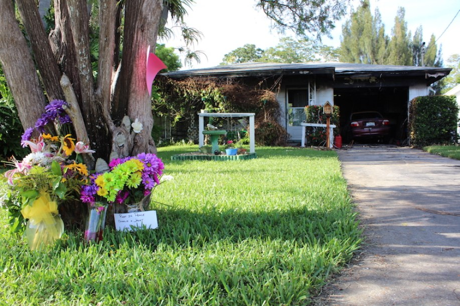 House with fire damage and flower memorial in front yard