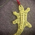 "A green ceramic gecko ornament with ""Gulfport"" written on it."