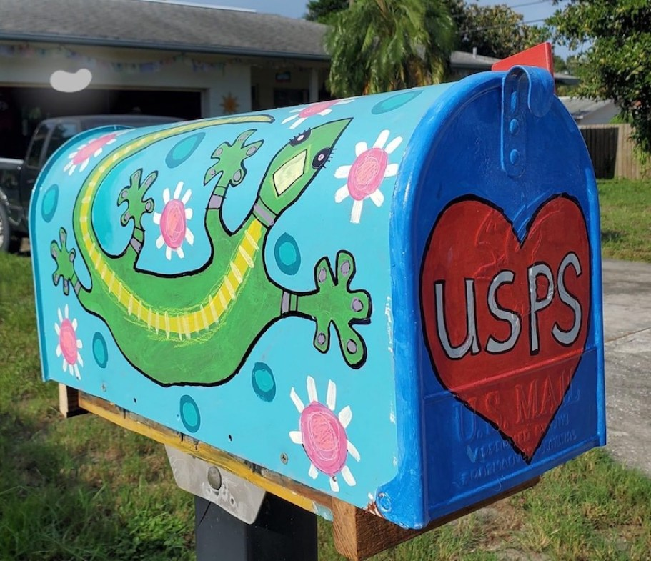 "A painted mailbox featuring a green gecko, pink flowers and a hear with ""USPS"" in the middle."