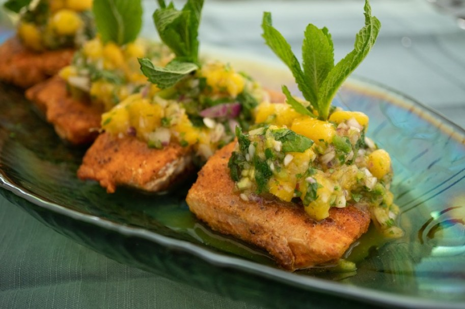 Salmon topped with mango salsa and green garnish on green plate