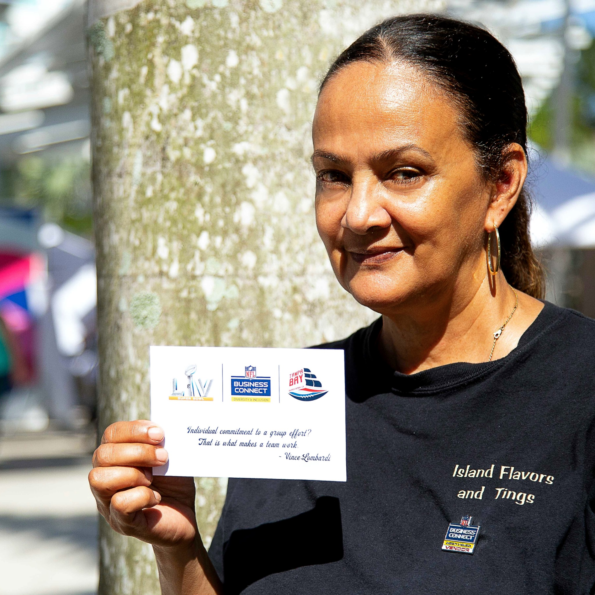 Helena Josephs wearing a black t-shirt holding her Business Connect invitation.