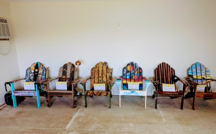 A row of artistically painted Adirondack chairs against a white wall indoors.
