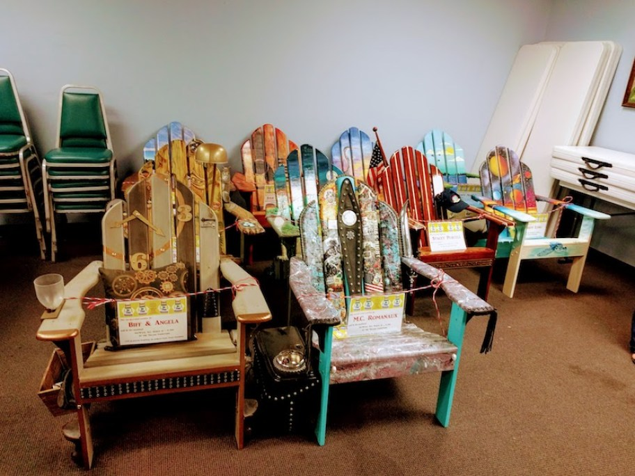 A grouping of artistically painted Adirondack chairs with small signs on them (unreadable)