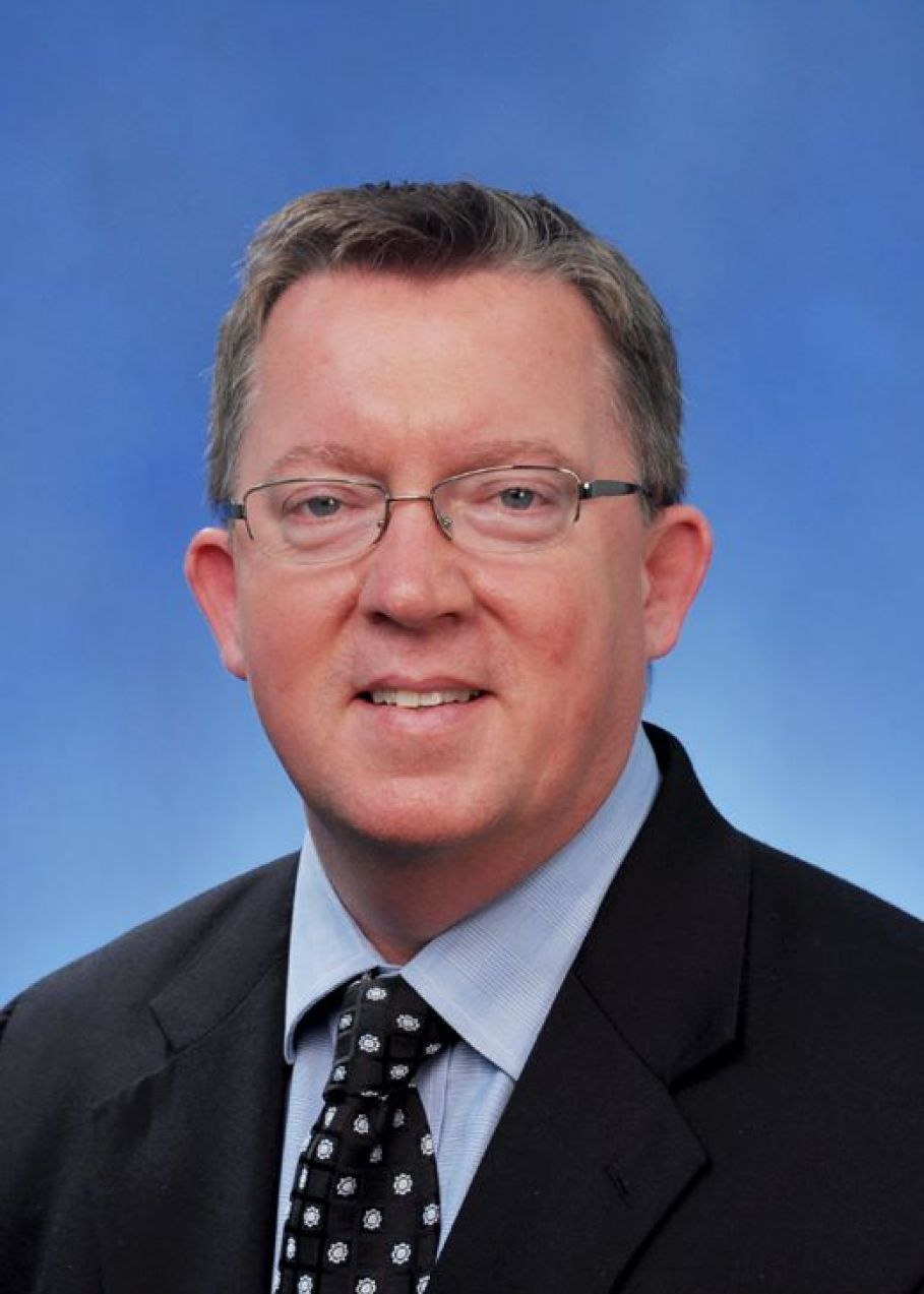 Head shot of a man with glasses in a suit with a blue background.