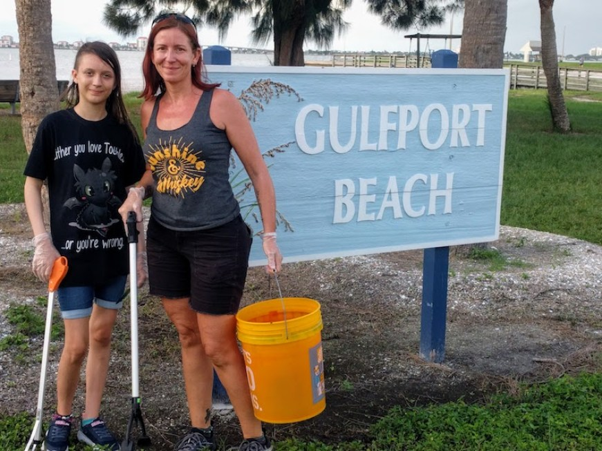 "A woman with an orange bucket and trash picker stands with a younger woman in front of a sign that reads ""Gulfport Beach"""