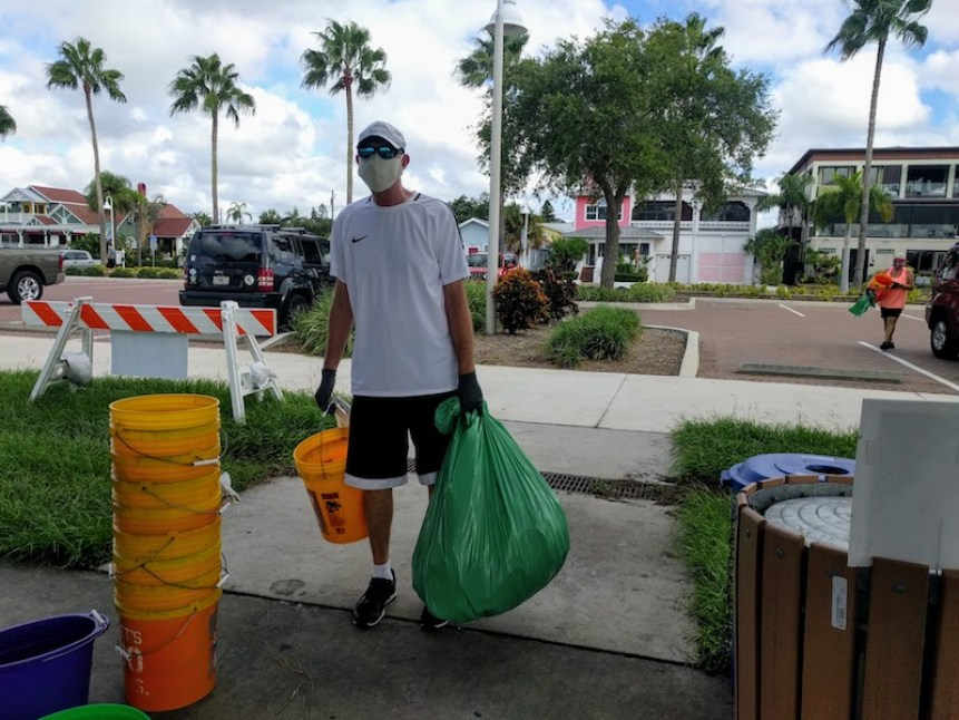 A man in a ball cap, facemask, white t-shirt and black shorts carries a green garbage bag and orange bucket.