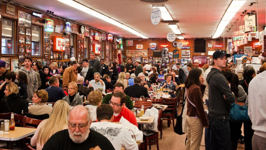 A photo of a crowded restaurant with people standing and sitting.