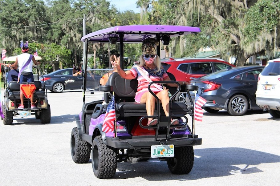 A woman in American flag clothes waves from the back of a golf cart driving down a road.