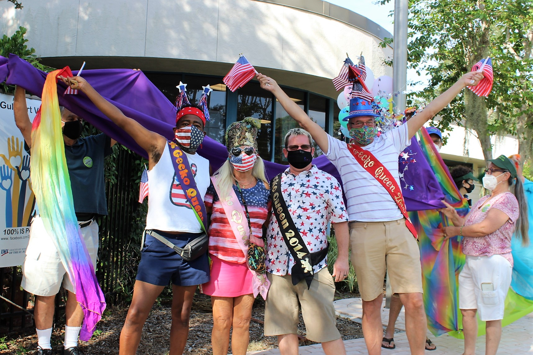 Four people in bright colors and sashes raising their arms in celebration.