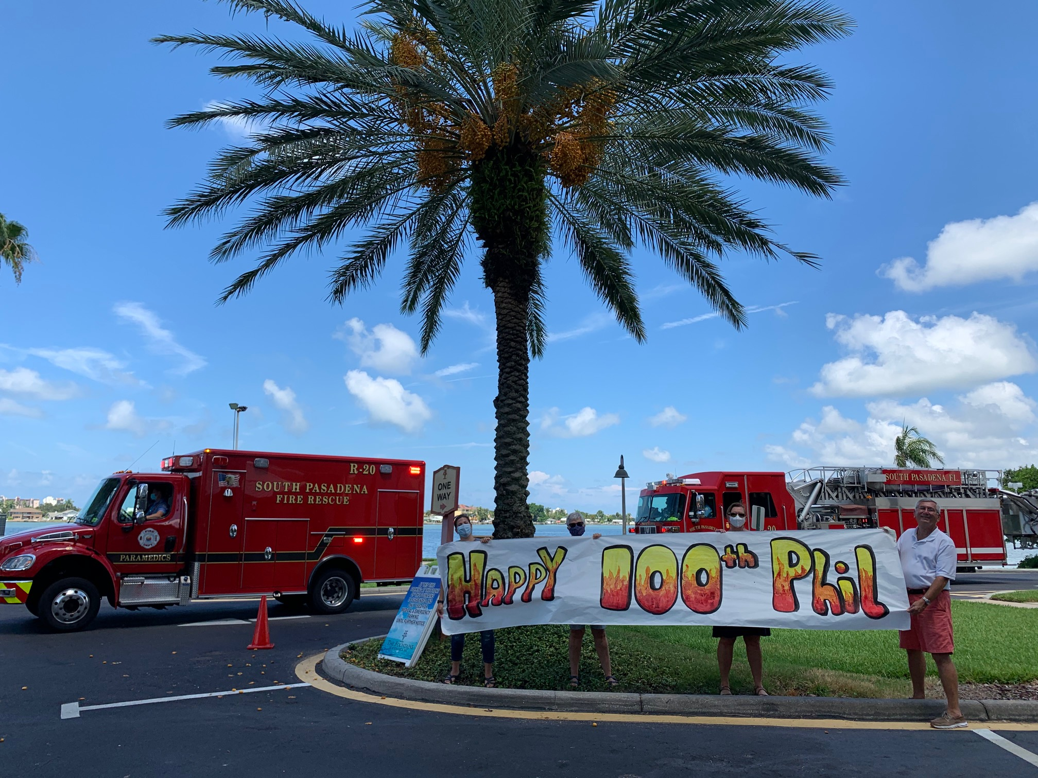 "Fire trucks and a plan tree with people in the foreground holding a banner that reads ""Happy 100th Phil."""