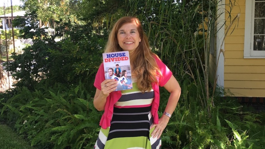 "A woman outside in a pink shirt holding a book with the title ""House Divided"""