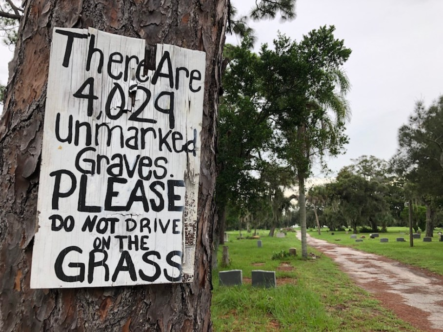 "A handprinted sign posted on a tree that reads ""There are 4029 unmarked graves, Please do not drive on the Grass."