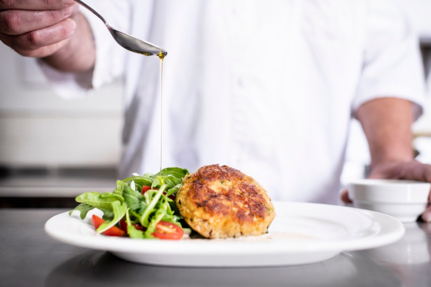A chef drizzling oil on a plate of crab cakes.