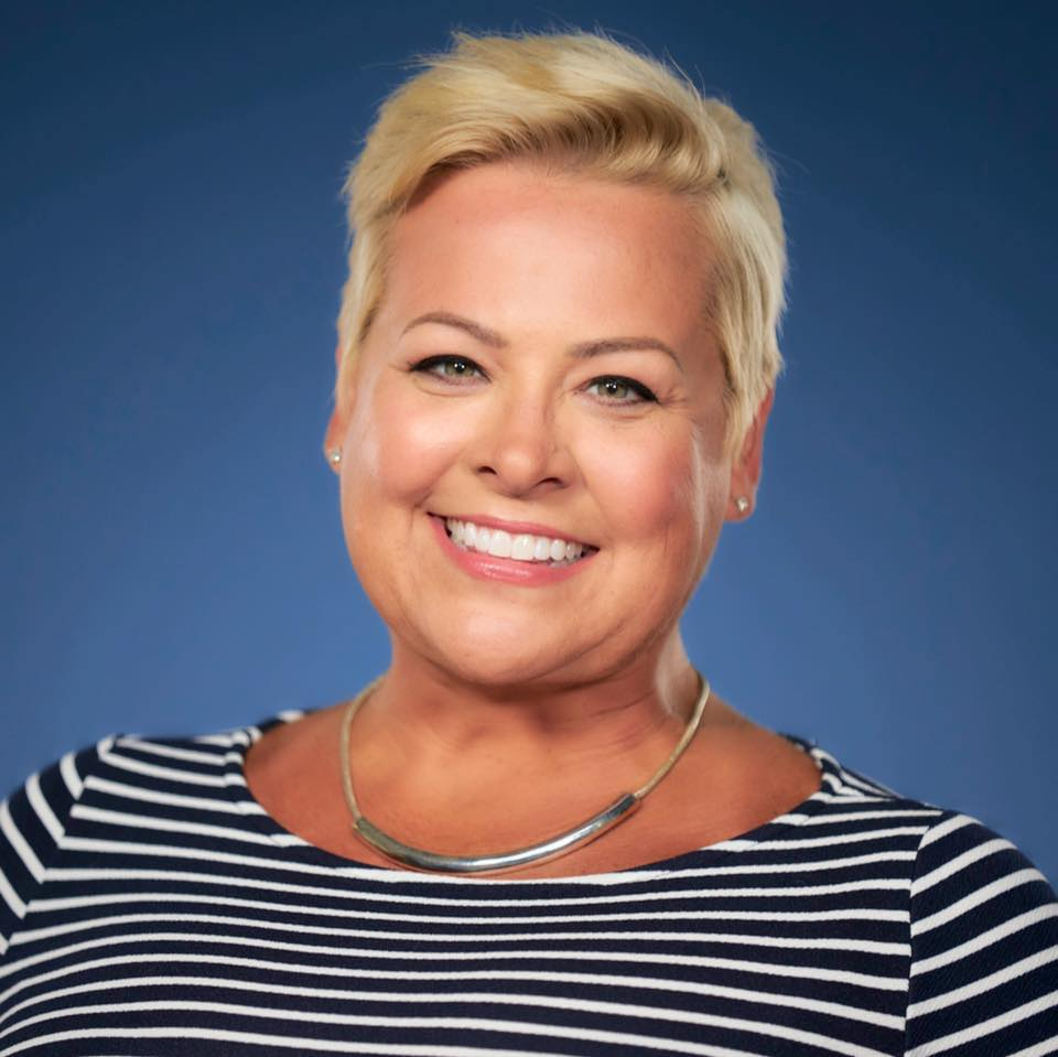 Head shot of a woman in a stripped shirt with a blue background.