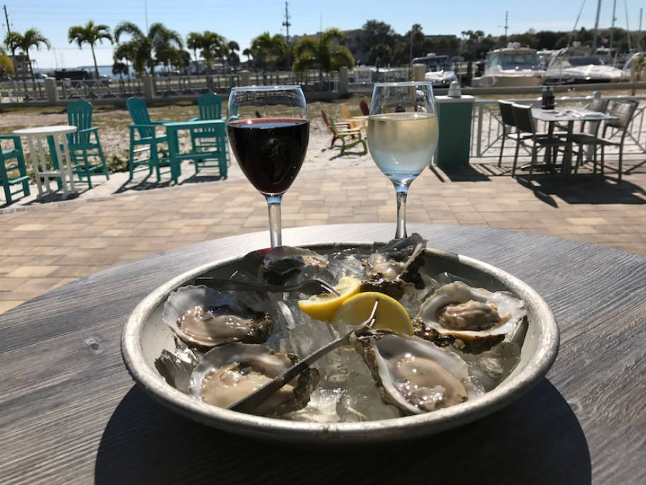 A red and white glasses of wine behind a plate of raw oysters at an outdoor venue