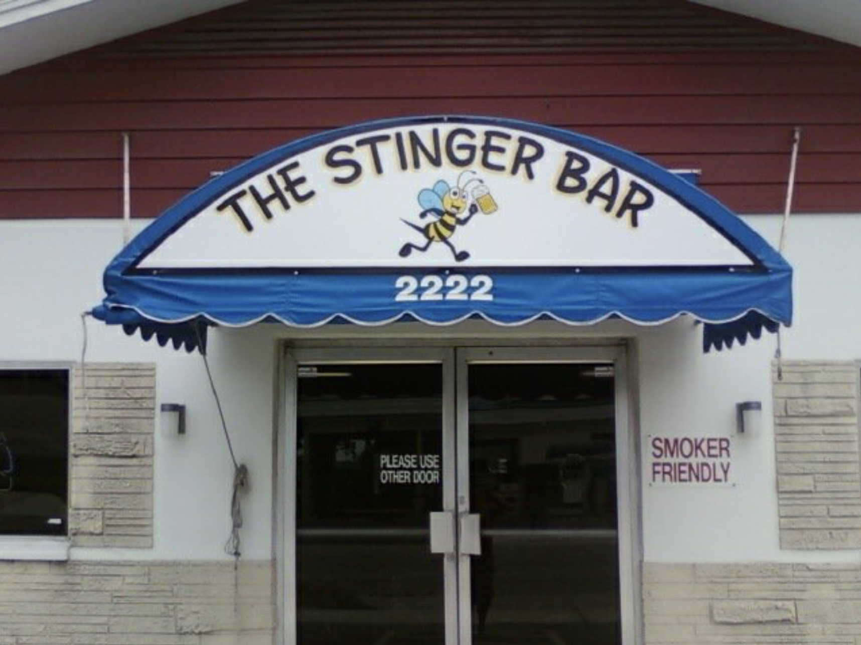 """The front entrance awning for The Stinger Bar that reads """"The Stinger Bar"""""""
