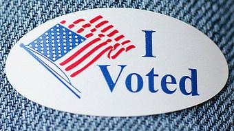 "A sticker with an American flag that reads ""I Voted."""