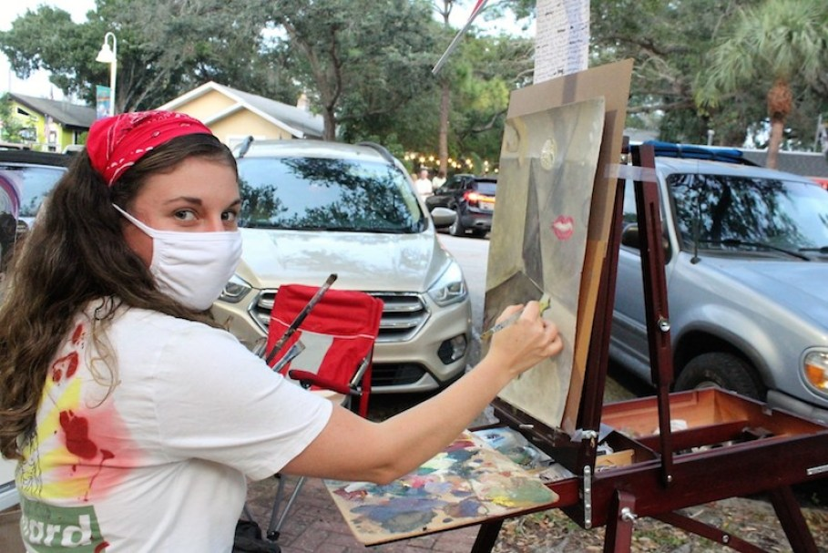 A woman with a mask looks at the camera while painting on an easel outdoors.