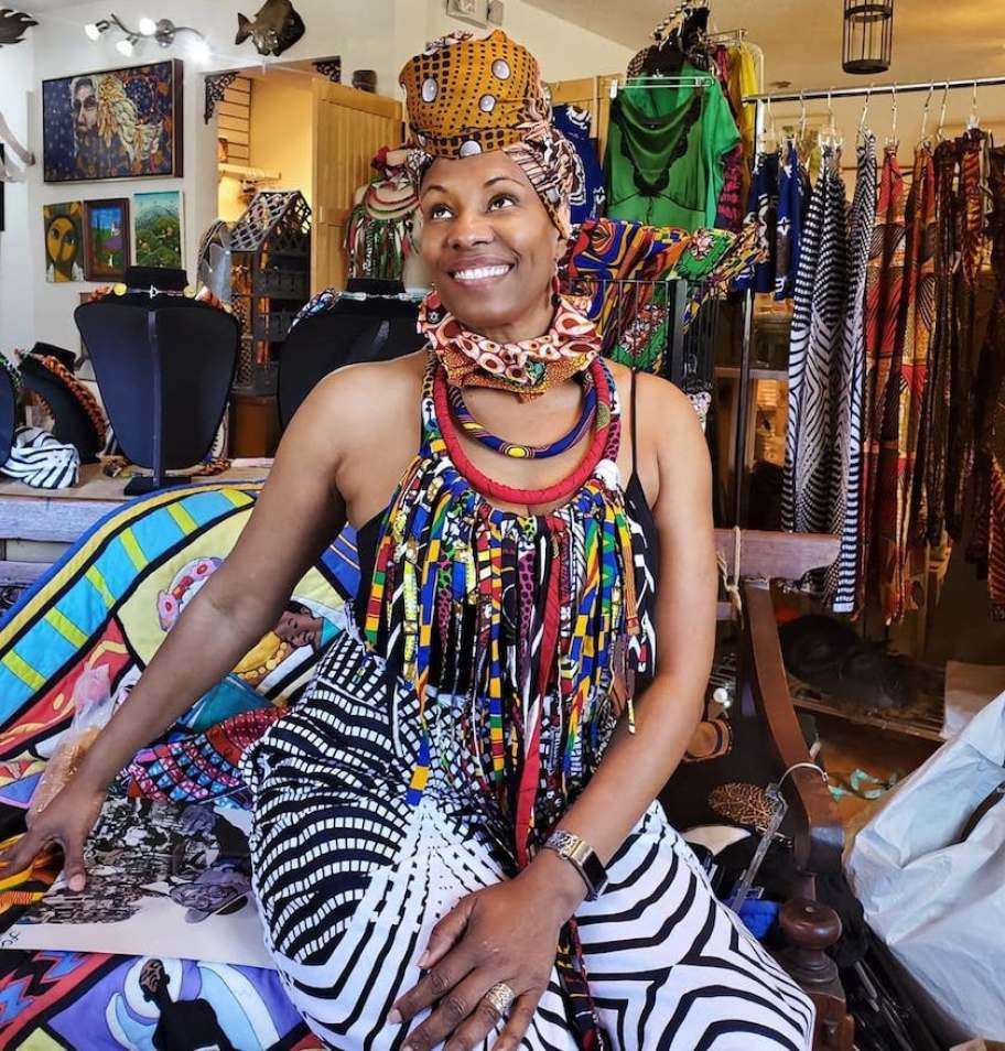 A woman in African textiles, jewelry and head covering smiling in a shop filled with colorful textiles.