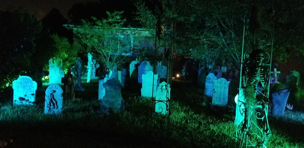 A fake cemetery in glowing blue light decorated for Halloween.
