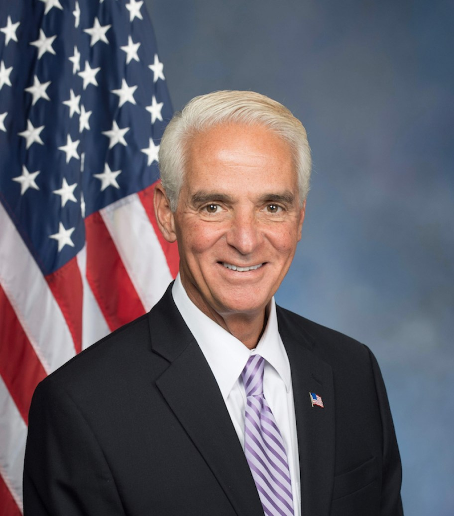 A photo of a man in a dark suit with stripped tie in front of a blue background and an American flag.