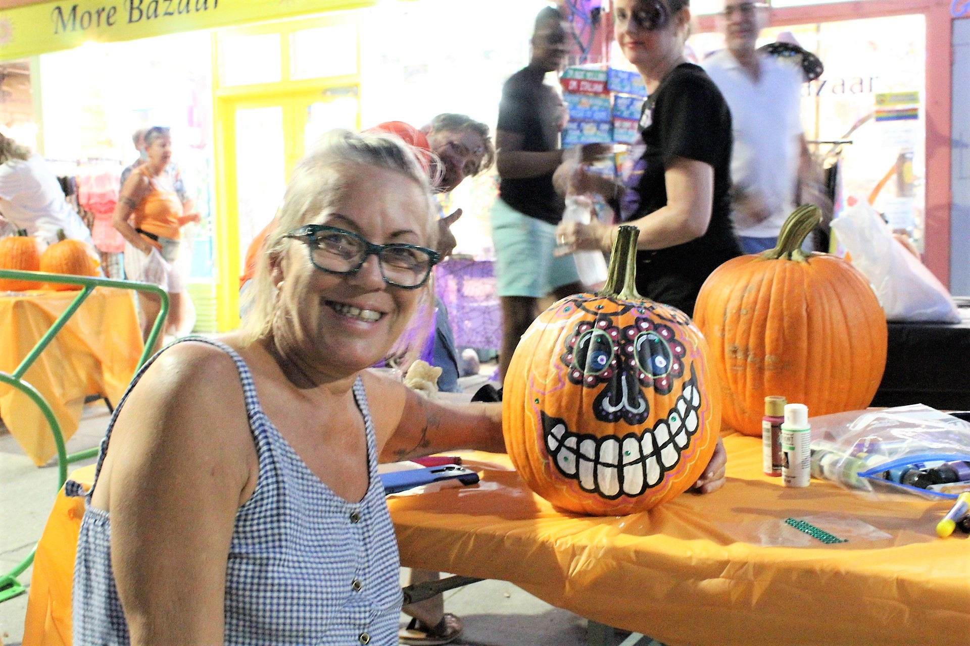 A woman smiles at the camera next to a painted Halloween pumpkin.