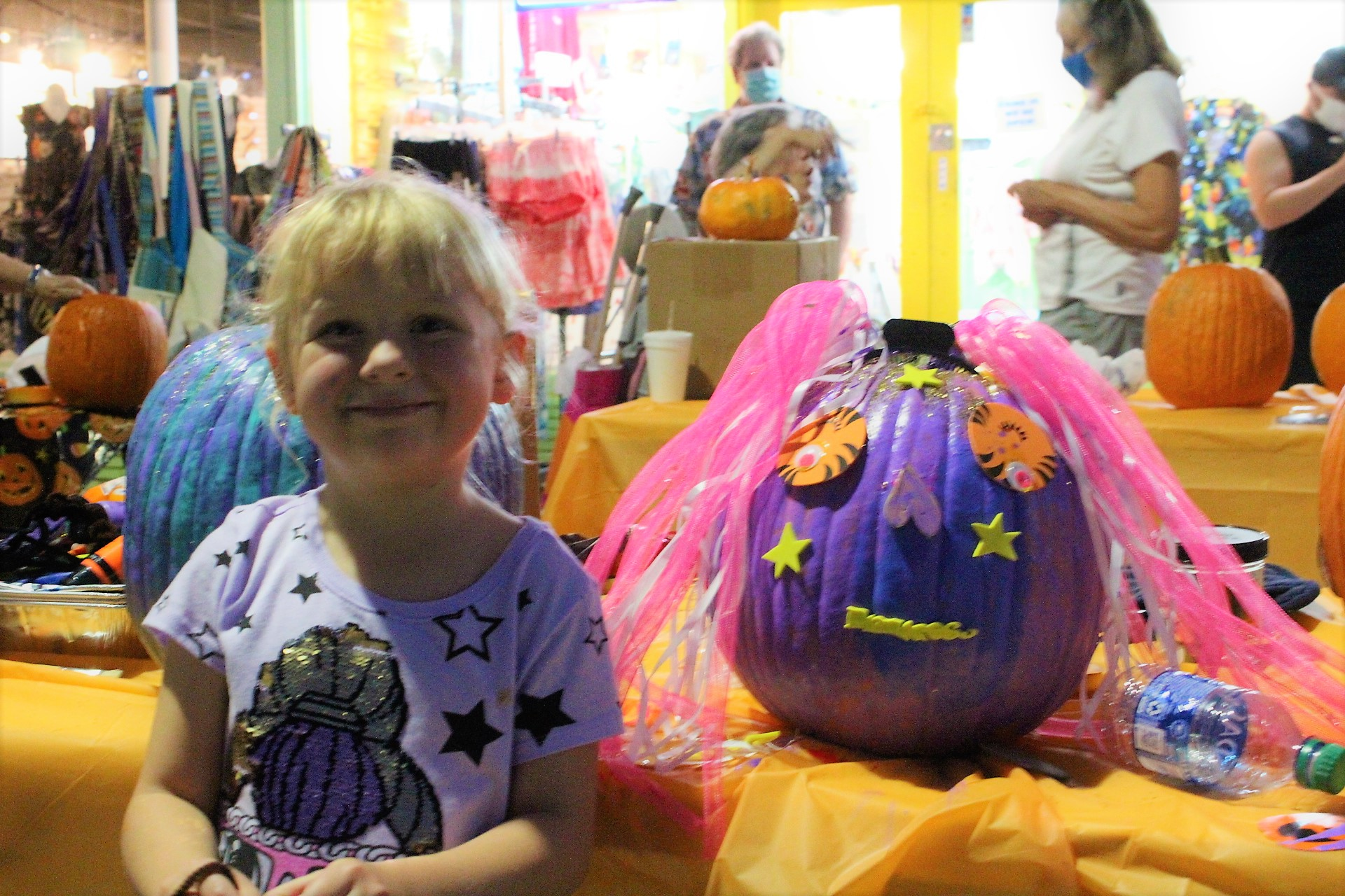 A small blonde child stands next to a purple painted and decorated pumpkin.