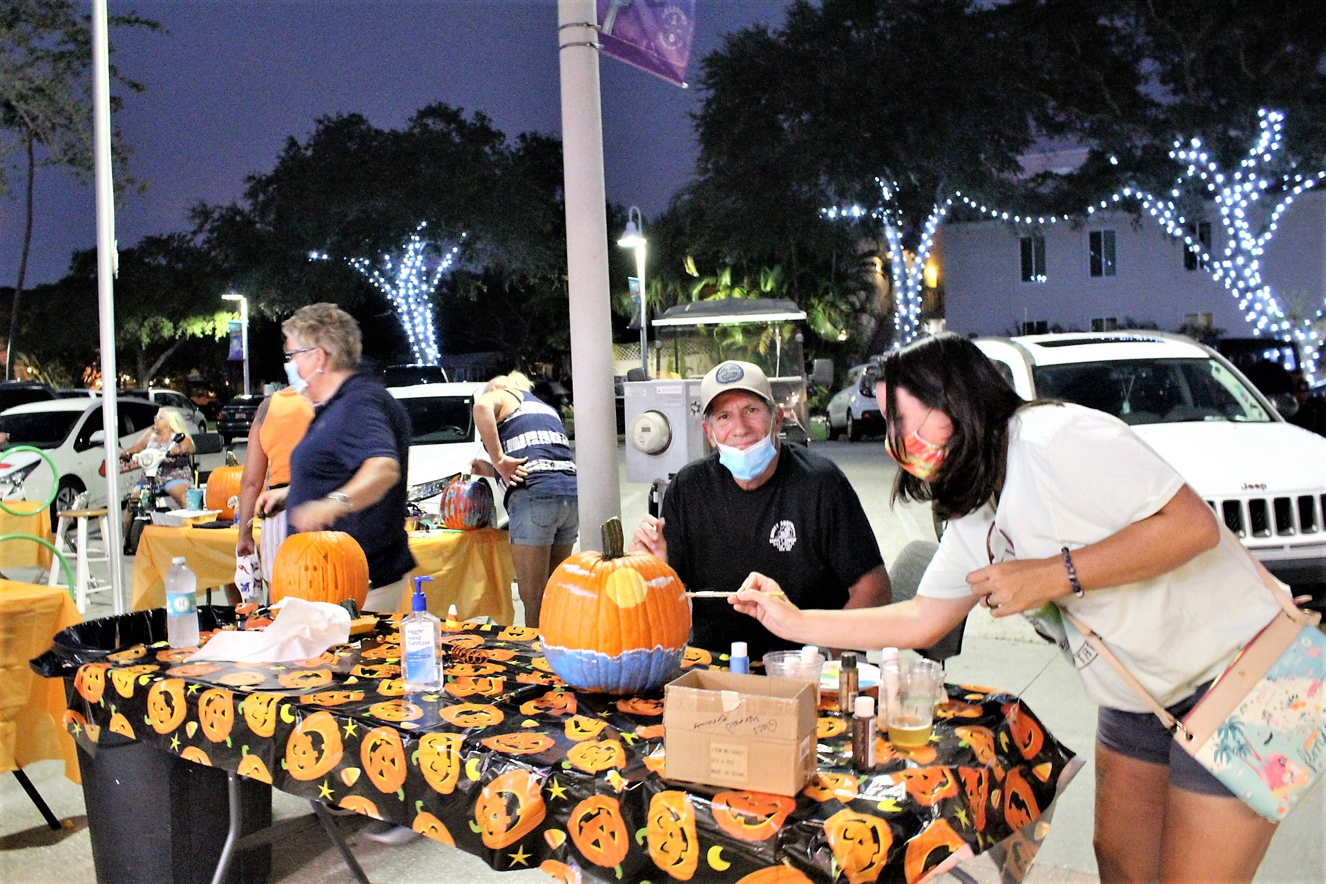 A group of people at an outdoor table at night decorating pumpkins over a pumpkin table cloth.