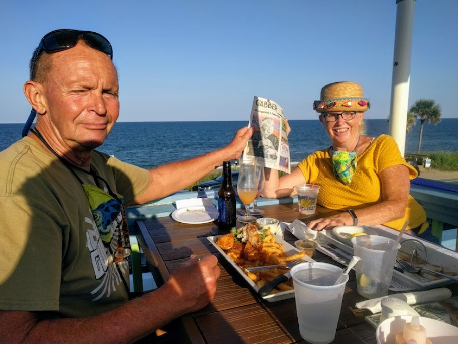 A man and a woman sit at a table on the water with food and a Gabber Newspaper.