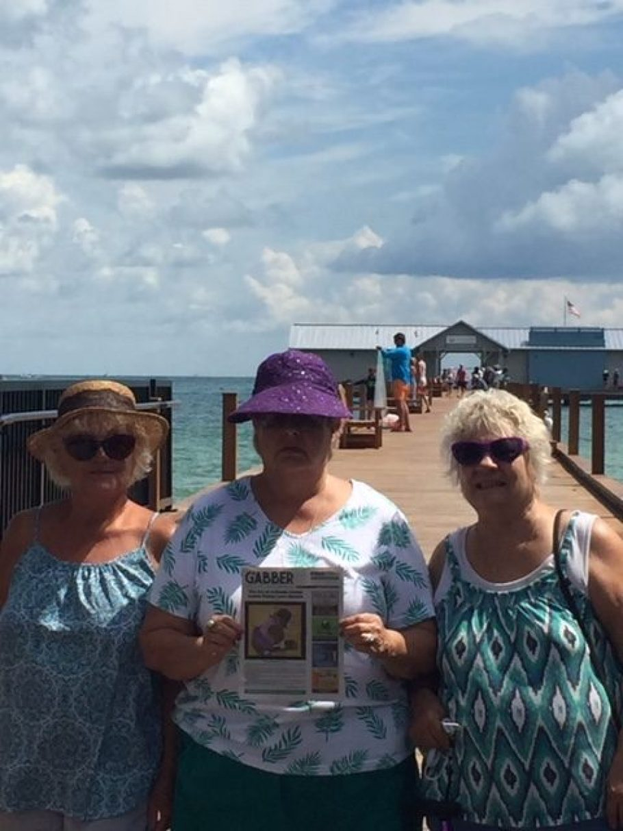 Three women with a Gabber newspaper stand in front of a dock by the water.