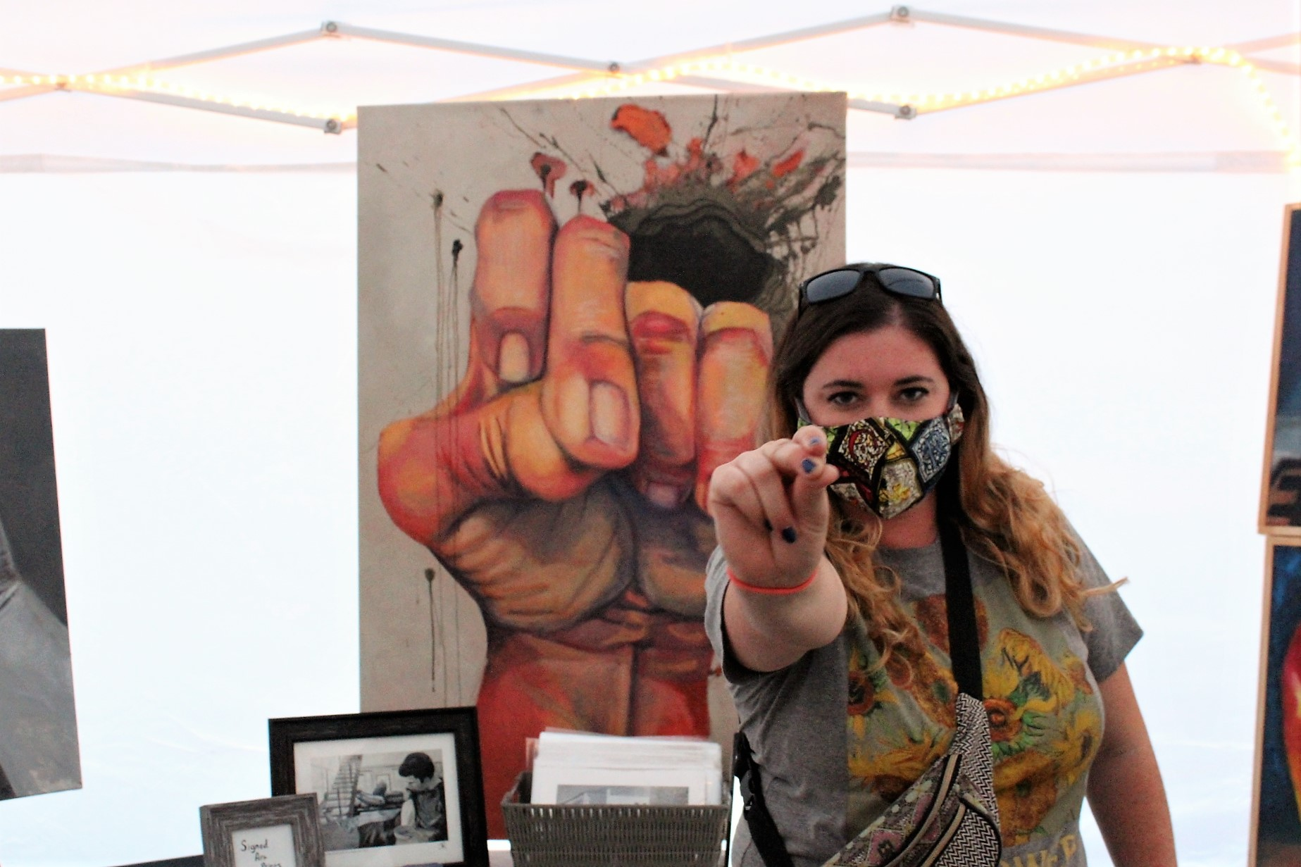 A woman with a face mask stands in front of a painting of a hand.