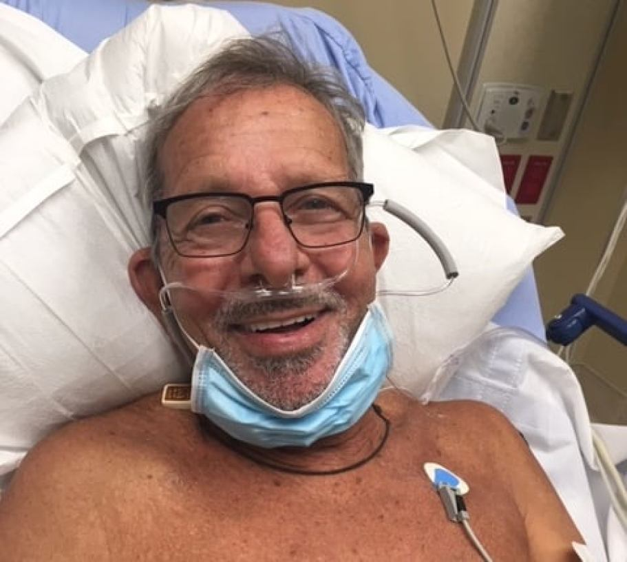 A man with bare chest in a hospital bed smiling at the camera.
