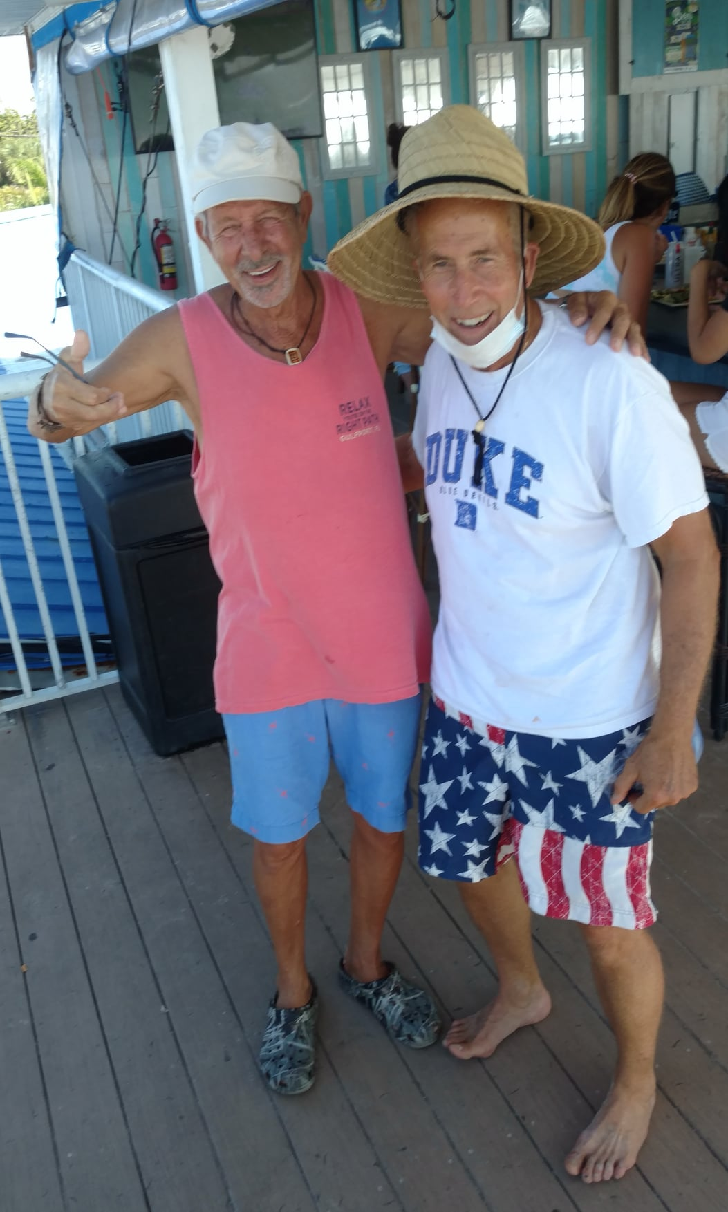 Two men in beach clothes with their arms around each others backs smile at the camera.