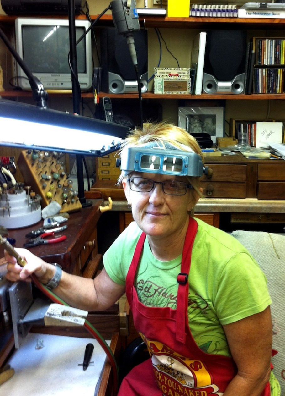 A woman with welder's glasses and a red apron smiling at the camera in a workshop.